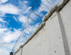 Prison wall with barbed wire and a watchtower on blue sky background
